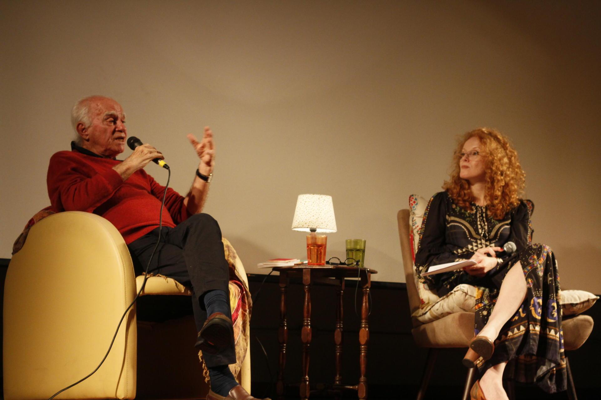 Foto colorida horizontal mostra em plano fechado, sentados em poltronas, o autor convidado falando ao microfone e ao lado uma mulher ruiva olhando para ele