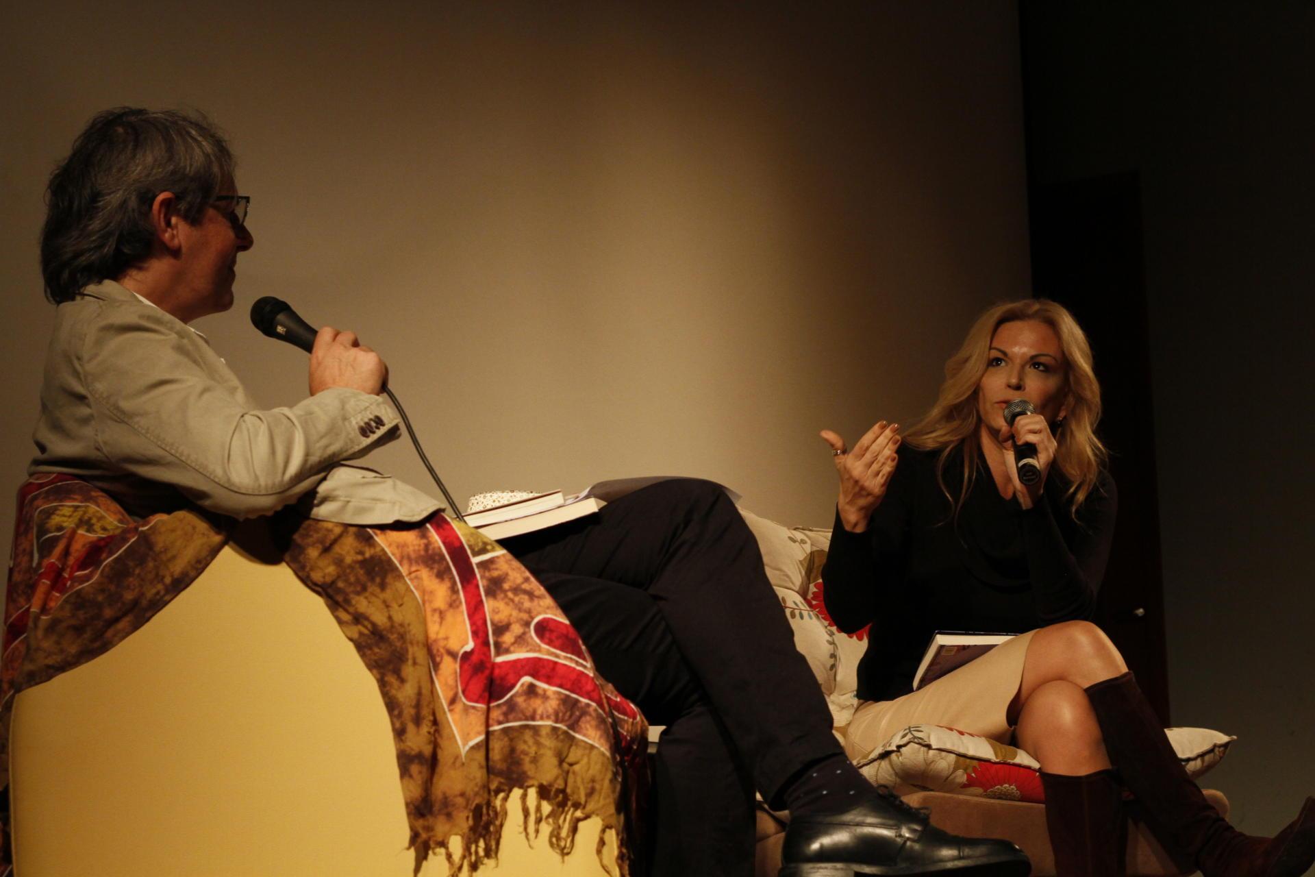 Foto colorida horizontal mostra duas pessoas sentadas, em primeiro plano, uma de lado, a escritora de frente, falando ao microfone e gesticulando, sob uma luz fraca