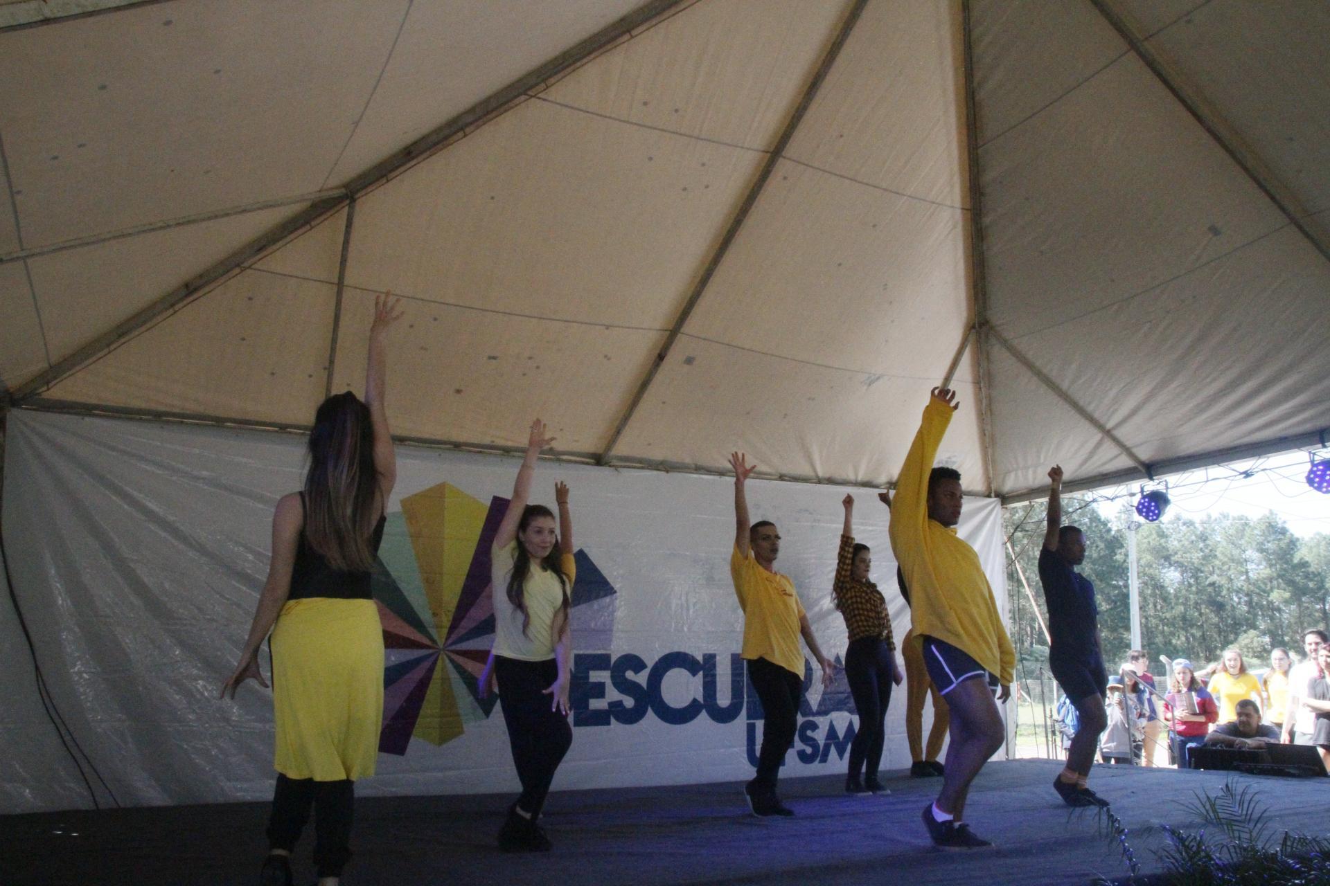 Foto colorida horizontal mostra alunos vestidos de preto e amarelo em movimentos de dança no palco ao fundo banner com logo do descubra ufsm