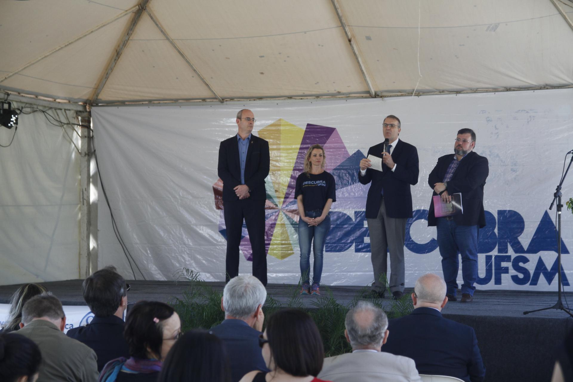 Foto colorida horizontal mostra quatro pessoas em pé no palco, um falando ao microfone, ao fundo banner com logo do descubra UFSM< e é possível ver algumas pessoas sentadas na platéia