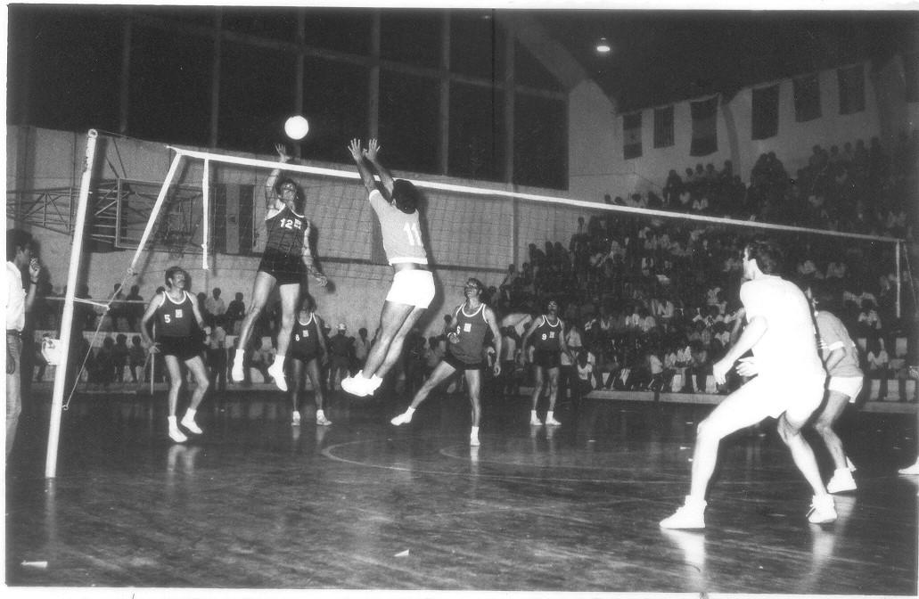 Foto em preto e branco mostra jogadores de volei jogando em uma quadra