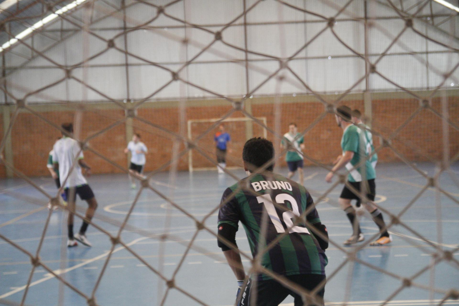 Foto colorida horizontal mostra homens jogando futsal em uma quadra, a foto é feita por trás de uma rede da quadra