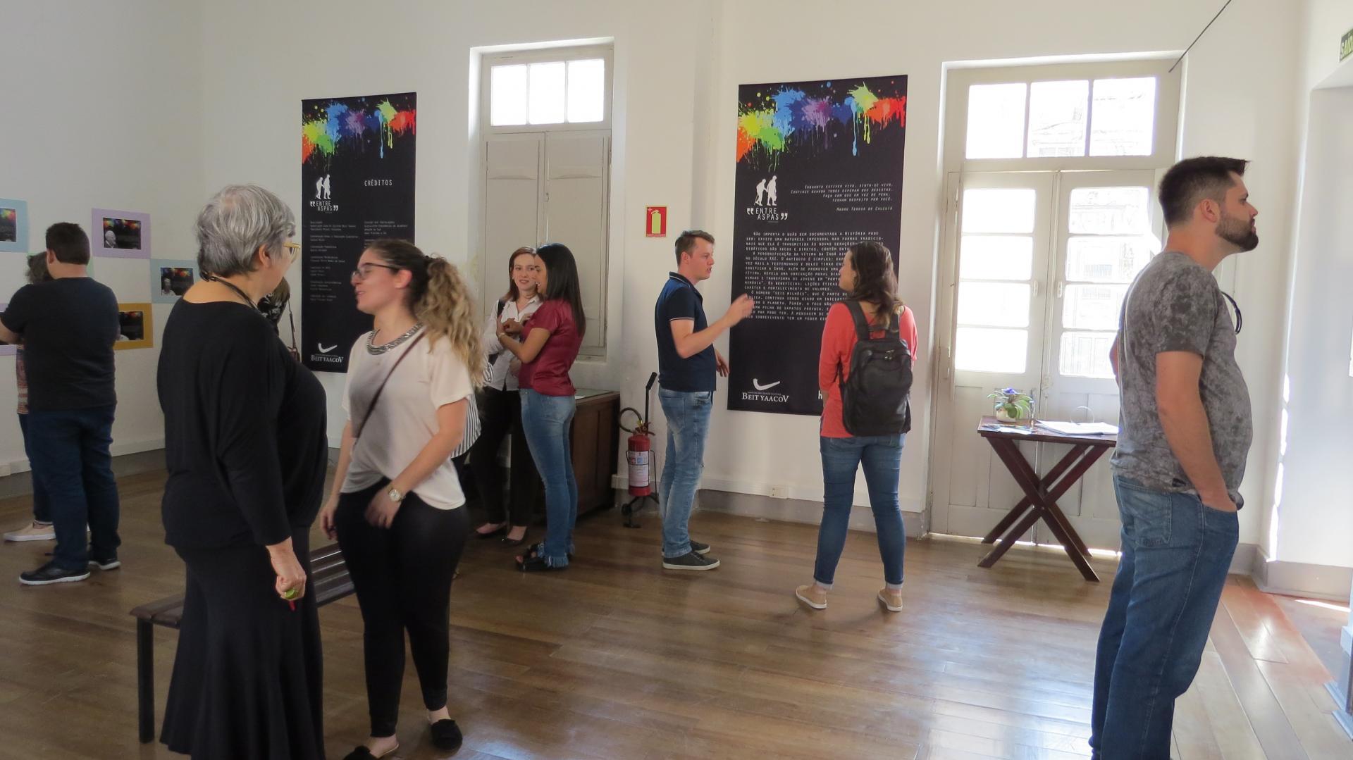 Foto colorida horizontal mostra pessoas em pé em uma sala branca, bem iluminada. Algumas falam entre si, outras apreciam os cartazes afixionados na parede