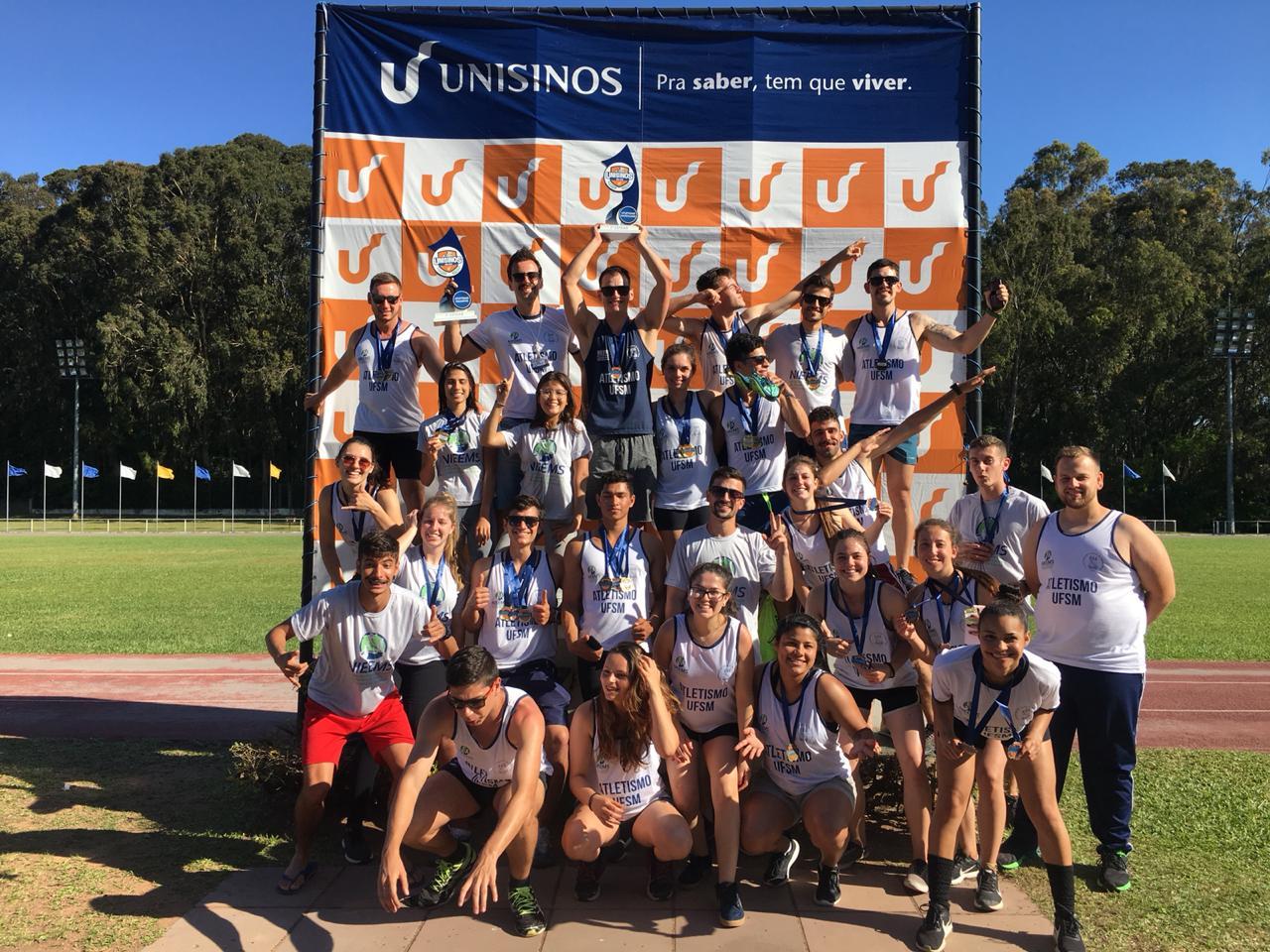 Foto colorida mostra uma turma de atletas em uma pista, em frente a um grande banner da unisinos, todos com regata do atletismo UFSM, alguns com medalhas