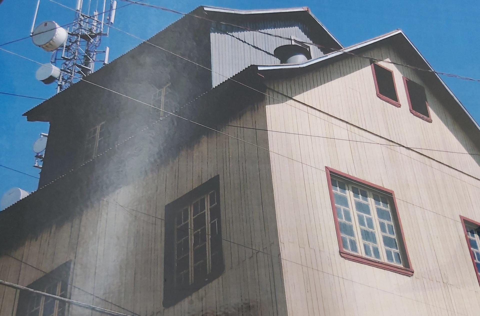 Foto colorida horizontal mostra uma casa de dois pisos de madeira, vista num ângulo abaixo, e atrás, por cima, uma moderna torre de telefonia