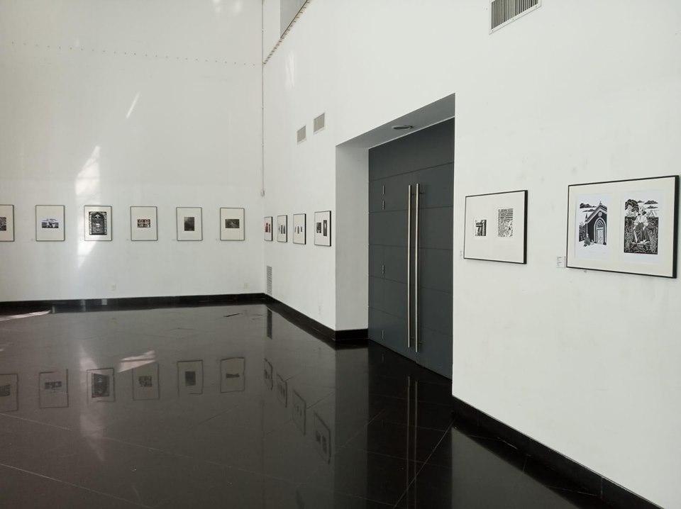 Foto em tons de branco e preto mostra os quadros com as gravuras dispostos em duas paredes brancas, em uma delas há uma grande porta escura