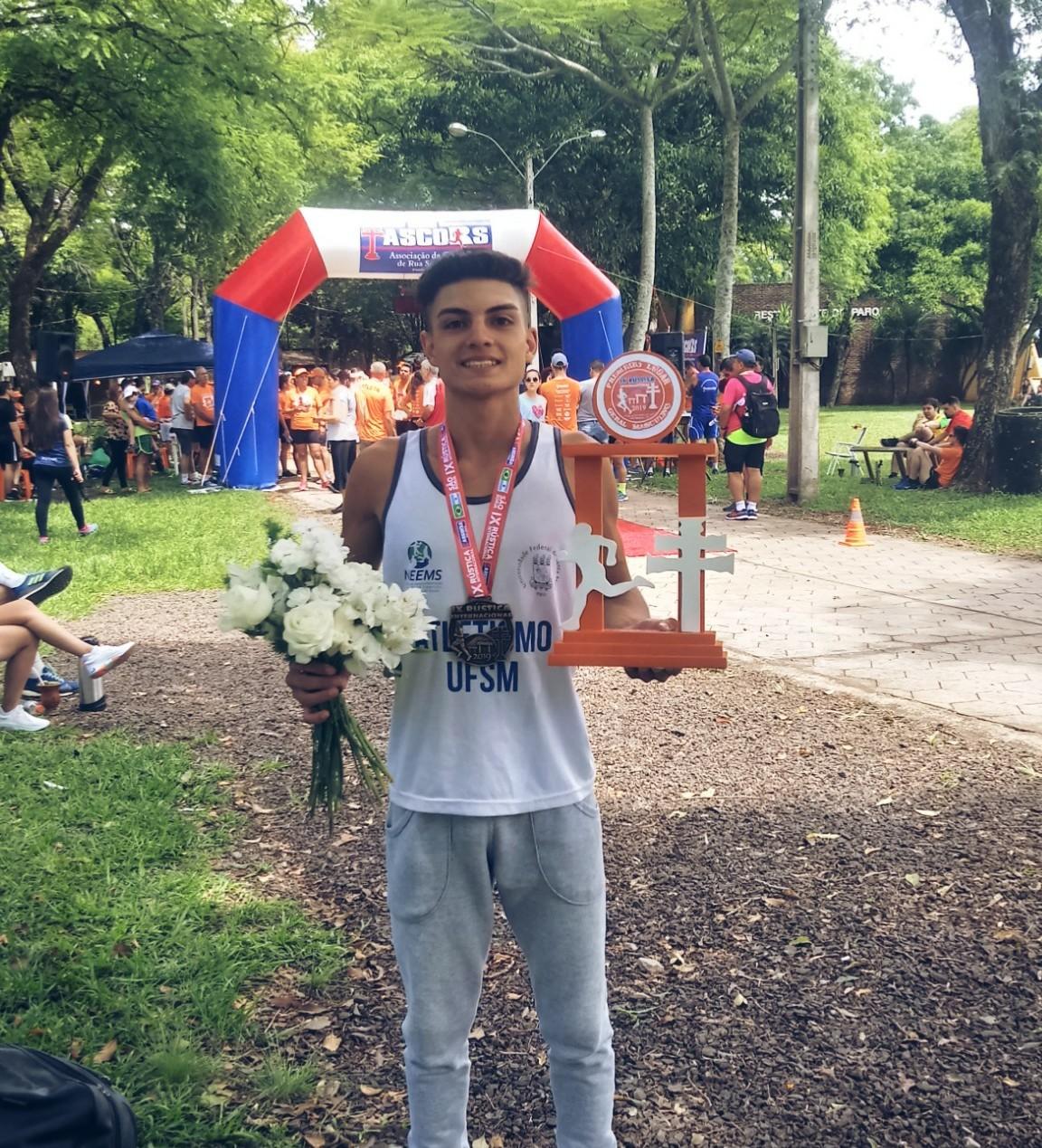 Foto vertical colorida mostra o atleta, vestindo camiseta do atletismo ufsm, segurando flores em uma mão e o troféu em outra