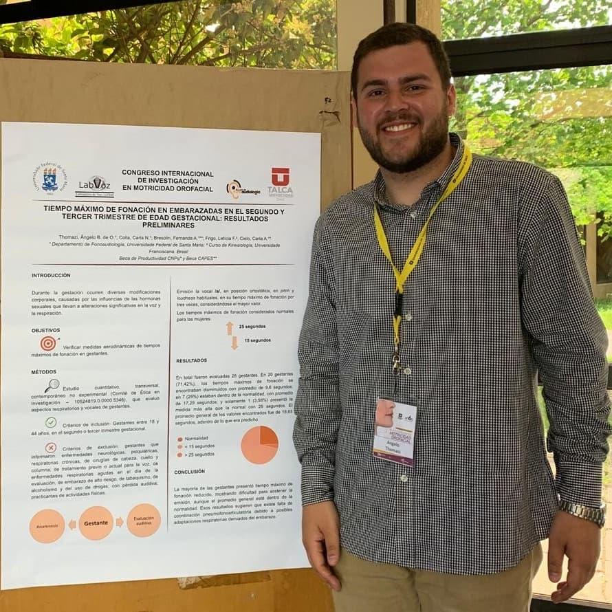 Foto colorida mostra o acadêmico posando ao lado do banner, ele está sorrindo, veste camisa xadrez e usa um crachá no pescoço, ao fundo há uma vidraça e atrás, árvores