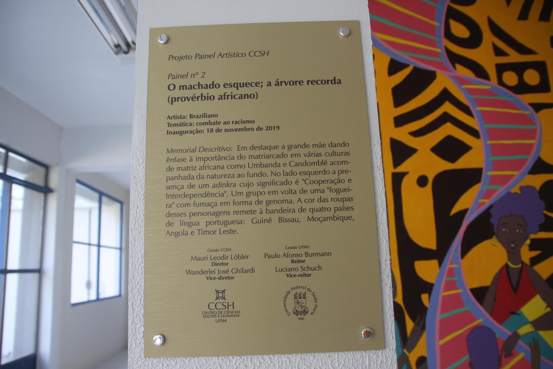 Foto colorida horizontal mostra em destaque uma placa explicativa, com o tema e descrição da obra, ao lado do painel