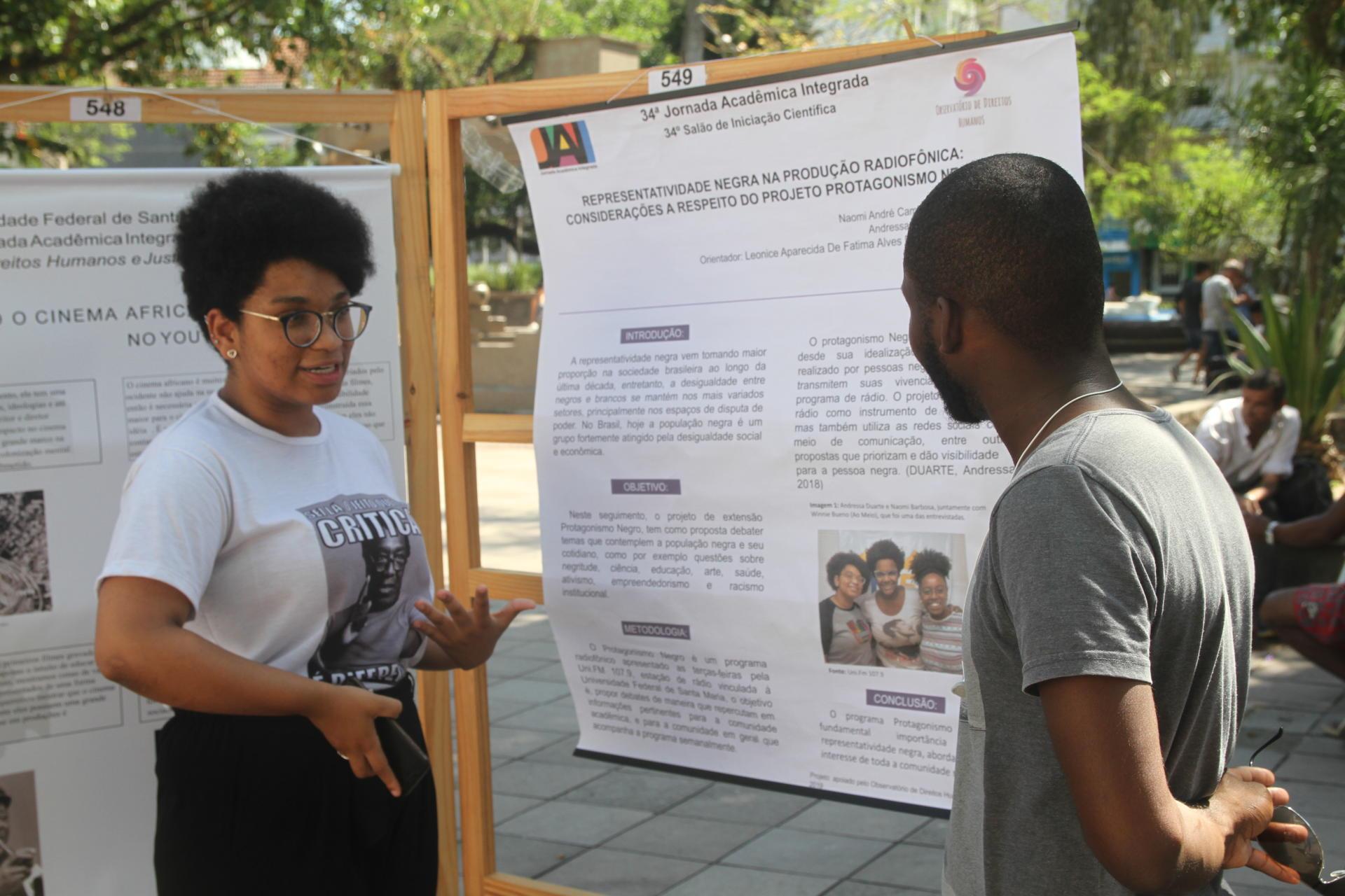 Foto colorida horizontal mostra estudante apresentando seu banner para um rapaz