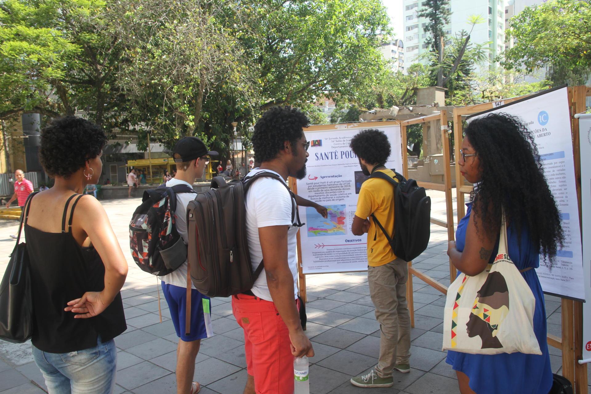 Foto colorida horizontal mostra pessoas olhando e apresentando banners na praça