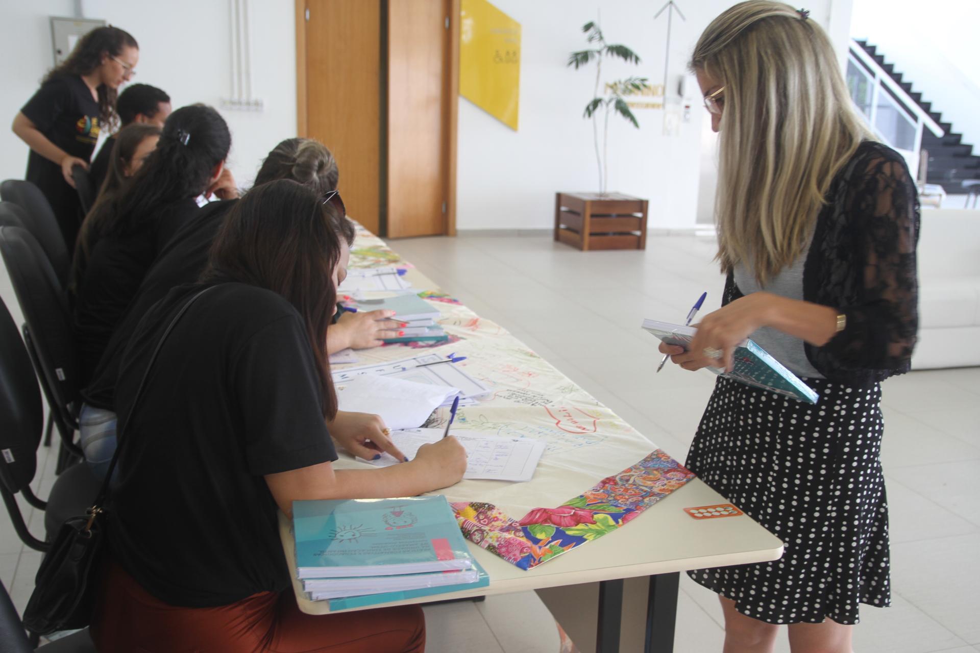 Foto colorida horizontal mostra uma mulher fazendo a inscrição na mesa de recepção do evento. Ela segura o livro recebido