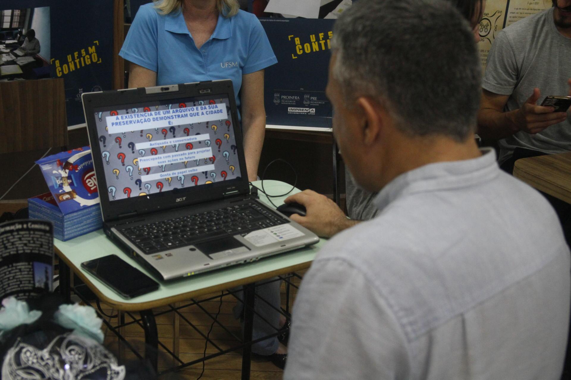Foto colorida horizontal mostra um homem de costas usando um computador respondendo um quizz