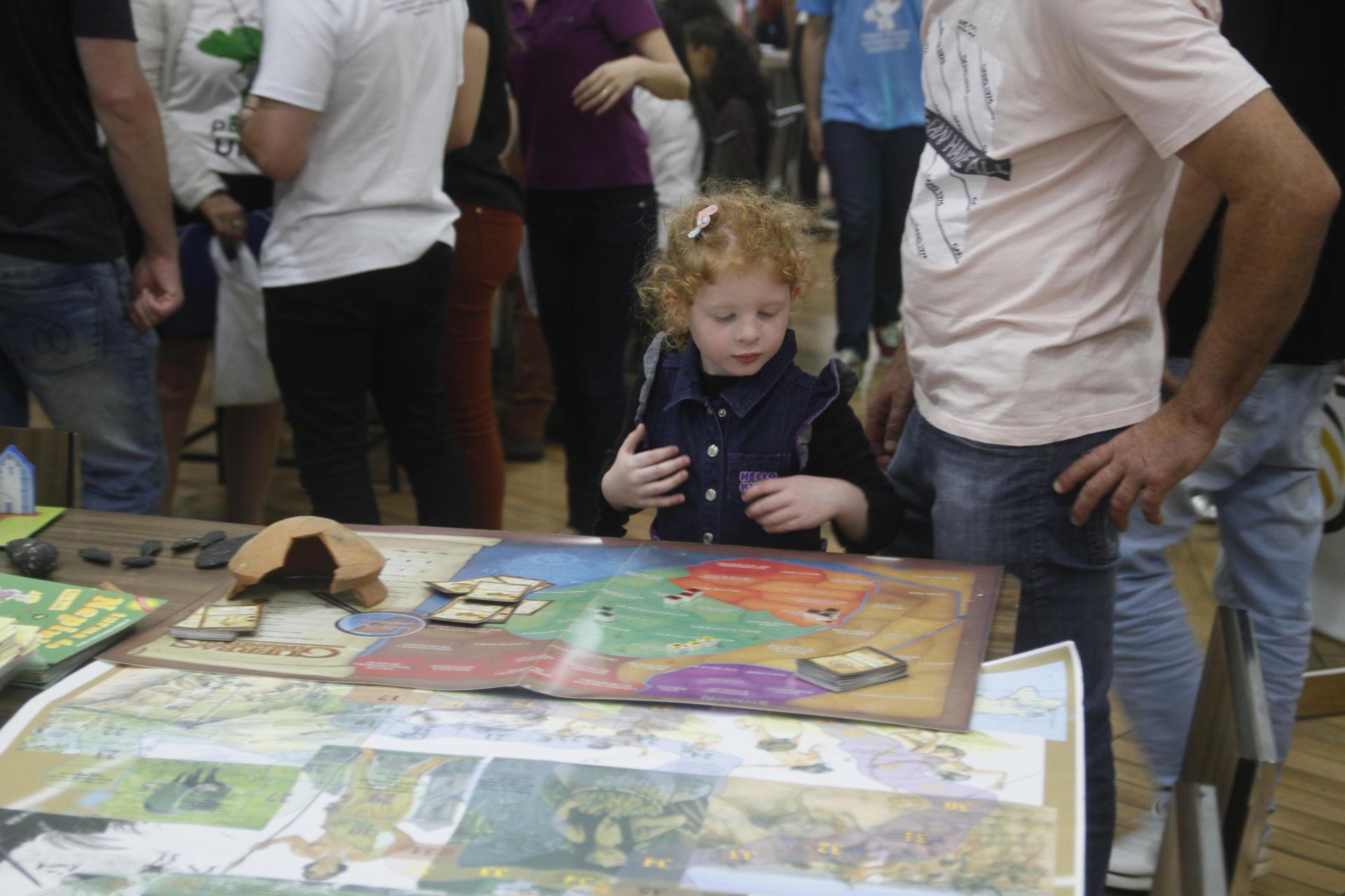 Foto colorida horizontal mostra uma criança olhando painéis e objetos dispostos em uma mesa