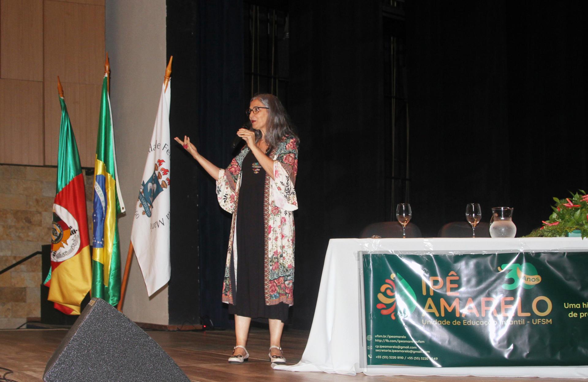 Foto colorida horizontal mostra uma pulher no palco do evento, ao lado de bandeiras e da mesa oficial com copos e um banner do evento. Ela fala ao microfone e gesticula com a outra mão