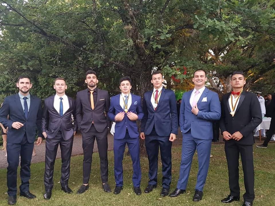 Foto colorida horizontal mostra sete homens perfilados lado a lado, todos vestindo terno e gravata em cores escuras, alguns com medalhas. Eles posam em uma área verde, à frente de uma árvore