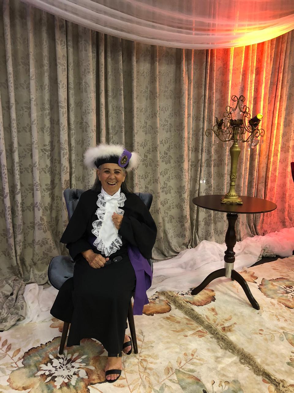 Foto vertical colorida mostra a formanda com vestes típicas sentada em uma poltrona em um fundo de cortinas e ao lado uma mesa com castiçal