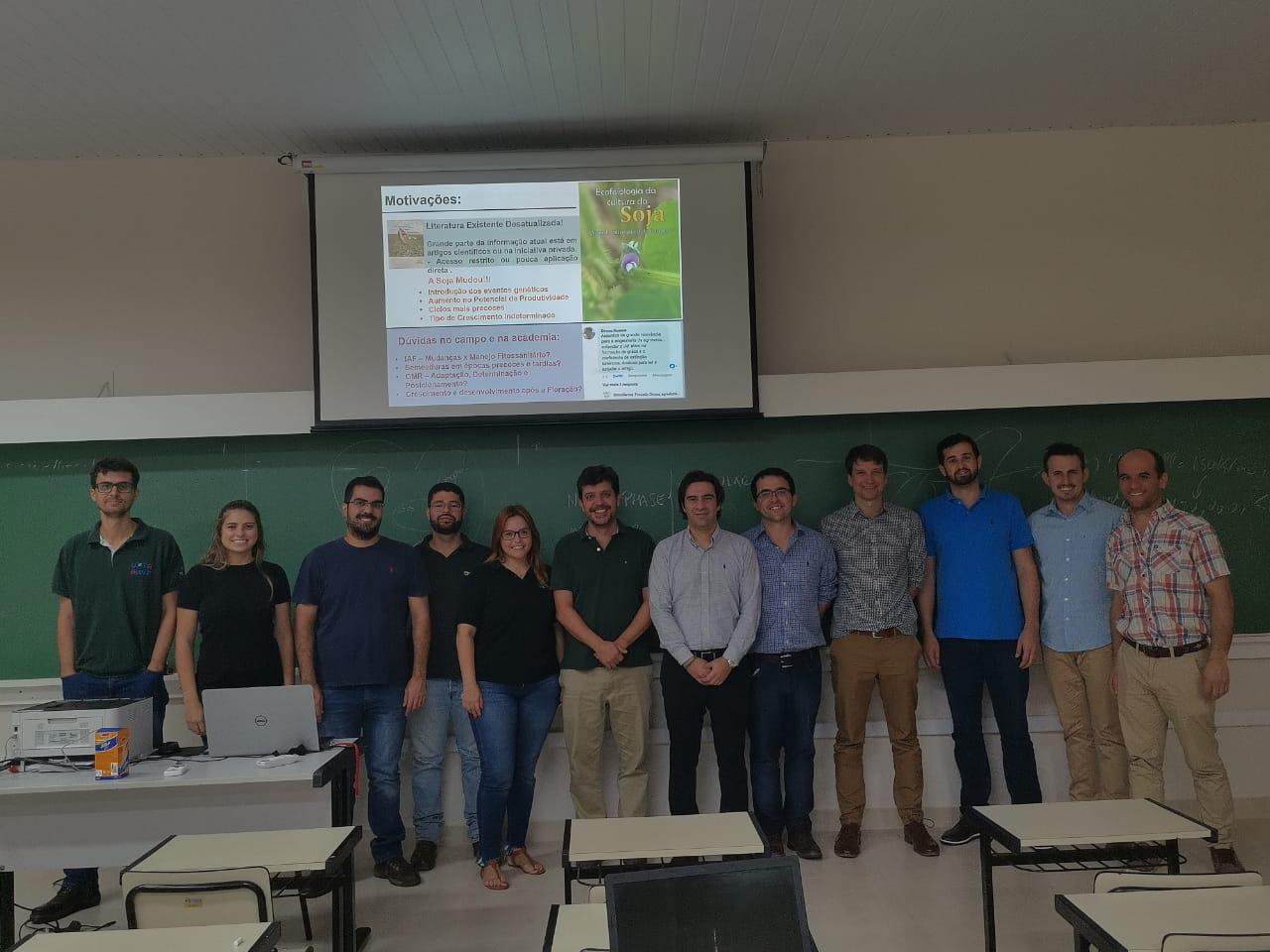Foto colorida horizontal com 12 pessoas lado a lado, posando para foto, em uma sala com um grande quadro verde e uma tela de slides ao fundo