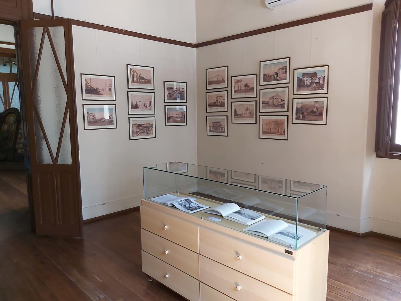 Foto colorida horizontal mostra quadros da exposição dispostos em duas paredes do museu, e à frente um expositor com livros em uma redoma de vidro