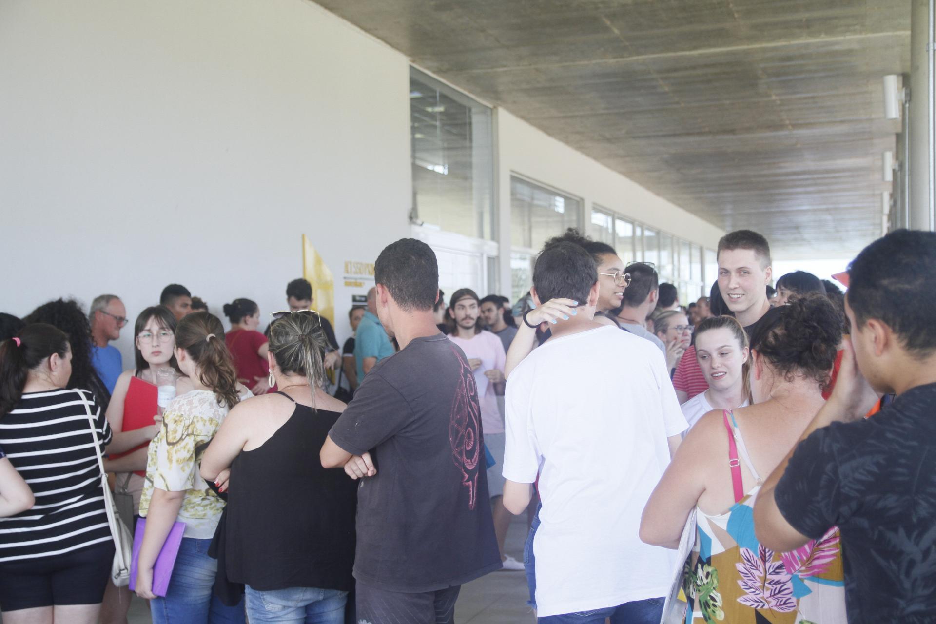 Foto colorida horizontal mostra diversas pessoas em filas no espaço na frente do Centro de Convenções
