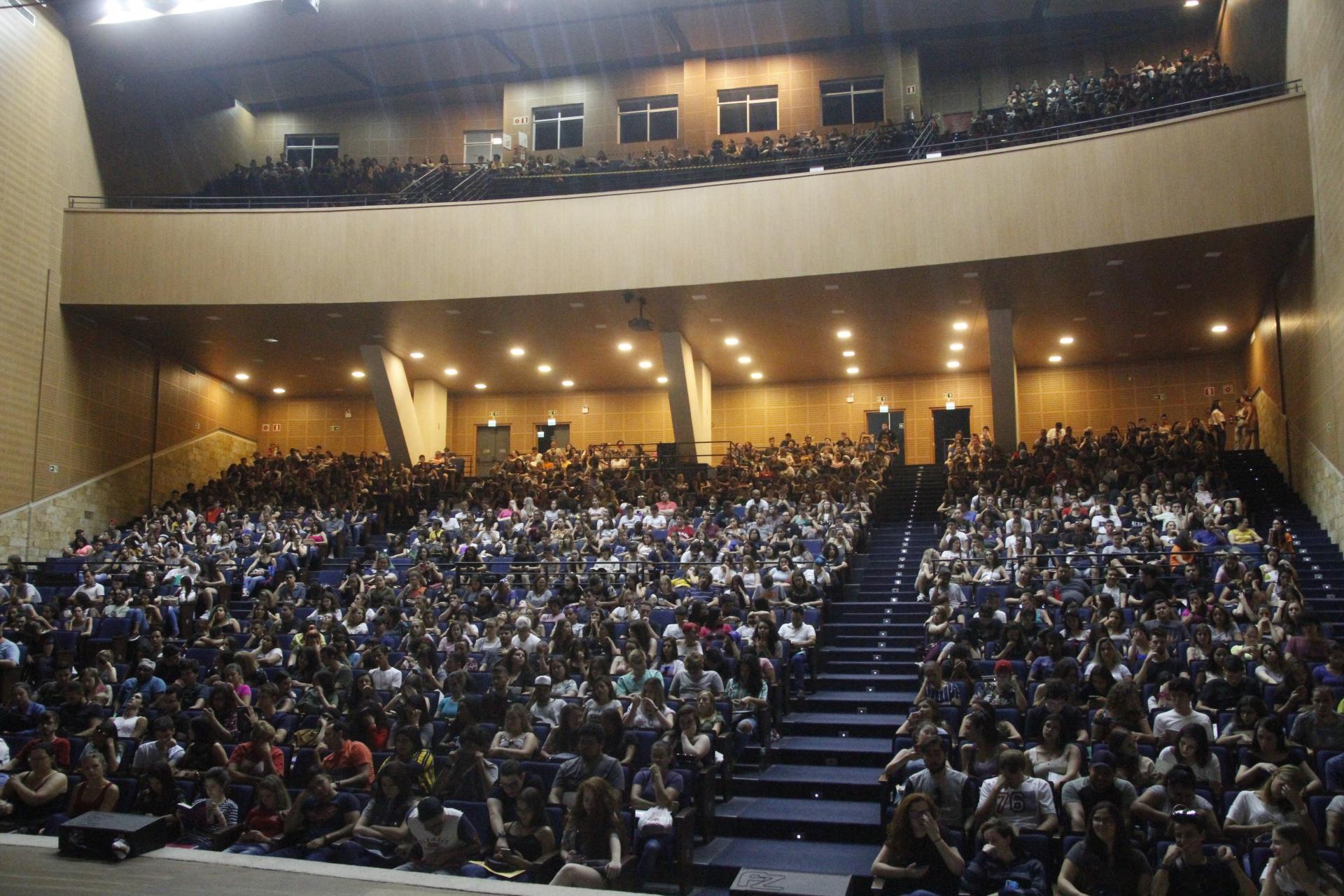 Foto colorida horizontal mostra o auditório do centro de convenções lotado