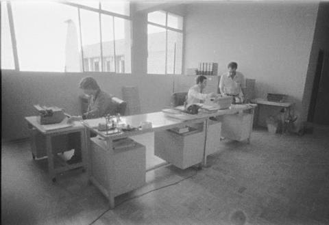 Foto preto e branca, bancada com três pessoas trabalhando