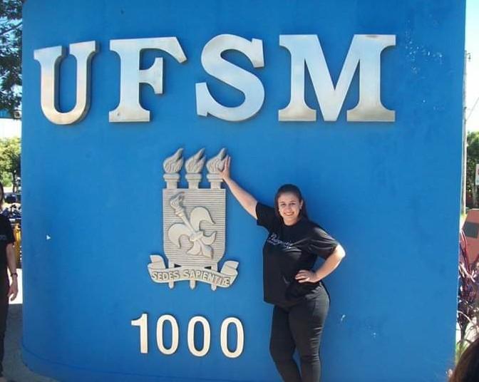 Foto horizontal da estudante vestindo preto em frente ao muro azul da UFSM com o brasão prateado