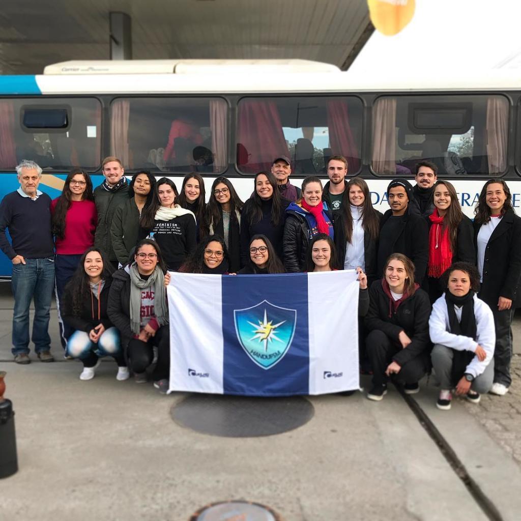 Foto rorizontal com turma segurando uma bandeira em frente a um ônibus da UFSM