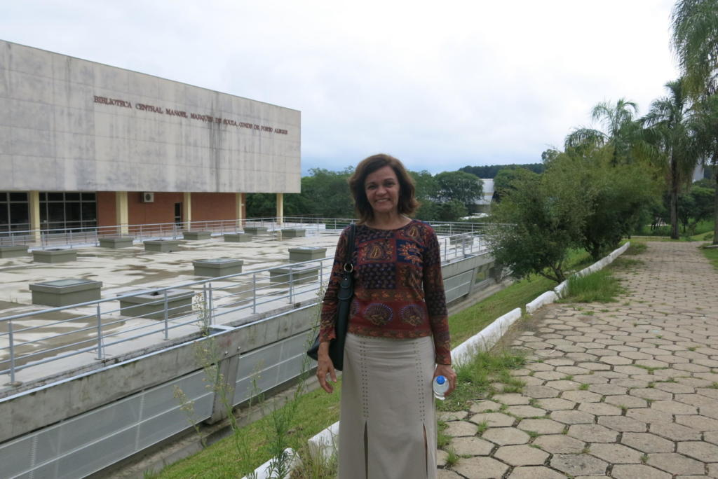 Foto horizontal, mulher em pé em frente à Biblioteca Central da UFSM