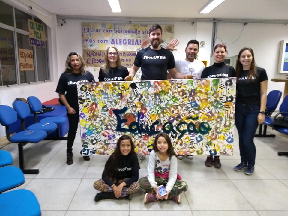 """Fotohorizontal, 6 pessoas em pé segurando um cartaz retangular escrito """"Educação"""" e duas pessoas sentadas em frente ao cartaz"""
