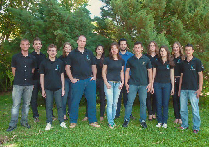 Foto horizontal com turma de alunos em pé em frente a árvores