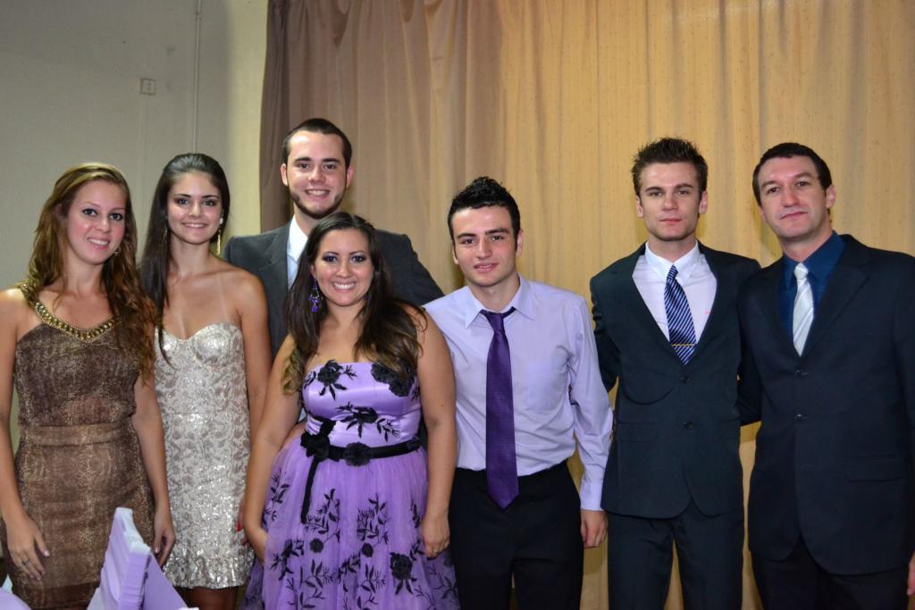 Foto horizontal com sete pessoas vestidas socialmente em pé