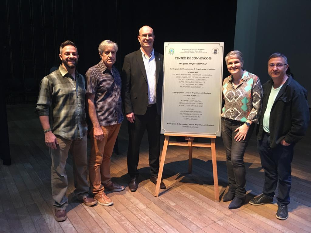 Foto horizontal com cinco homens, incluindo o vice-reitor Luciano Schuch, em torno da placa de inauguração do Centro de Convenções