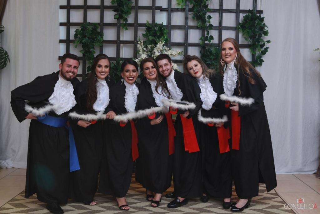 Foto horizontal de sete pessoas em pé, vestidas de toga no dia de sua formatura