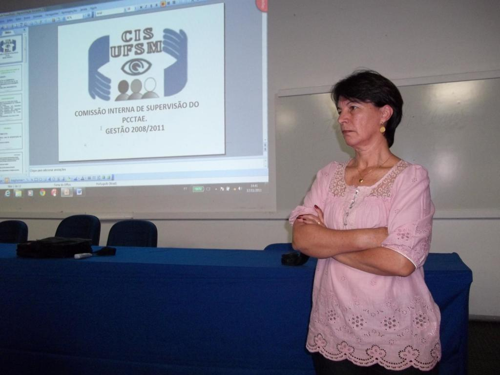 Foto horizontal, mulher em pé em frente à projeção em tela branca