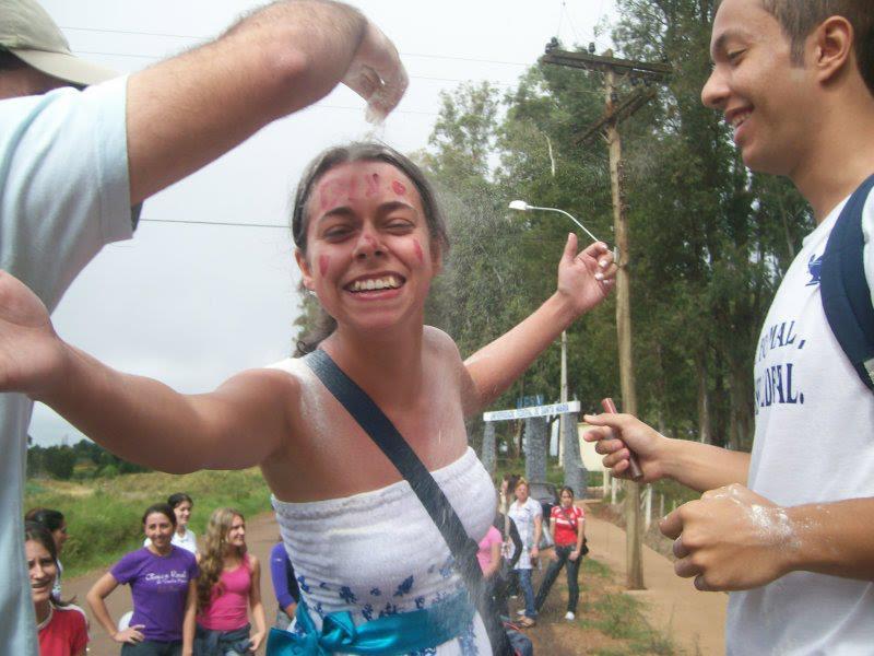 Foto horizontal. Mulher de braços abertos com rosto pintado, um braço jogando farinha nela e um rapaz sorrindo