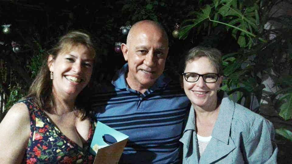 Foto horizontal, duas mulhere e um homem entre elas, os três sorrindo
