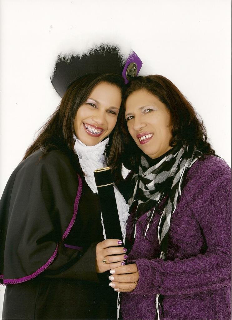 Foto vertical, duas mulheres abraçadas segurando um canuso de formatura, uma delas vestindo toga
