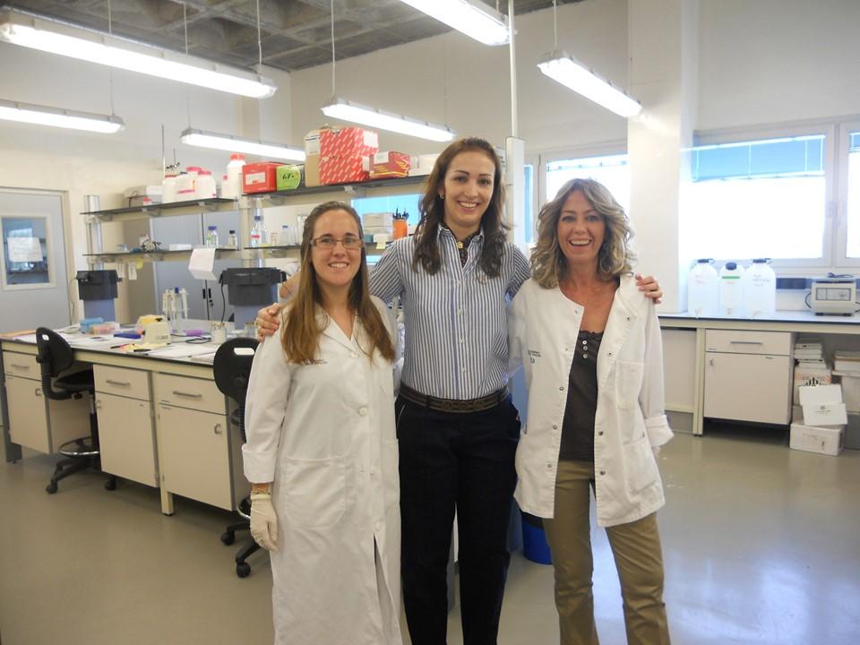 Foto horizontal com 3 mulheres em pé em um laboratório, duas vestem jaleco branco