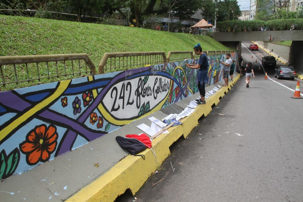 Foto horizontal de artistas grafitando o túnel Evandro Behr com a temática da Kiss