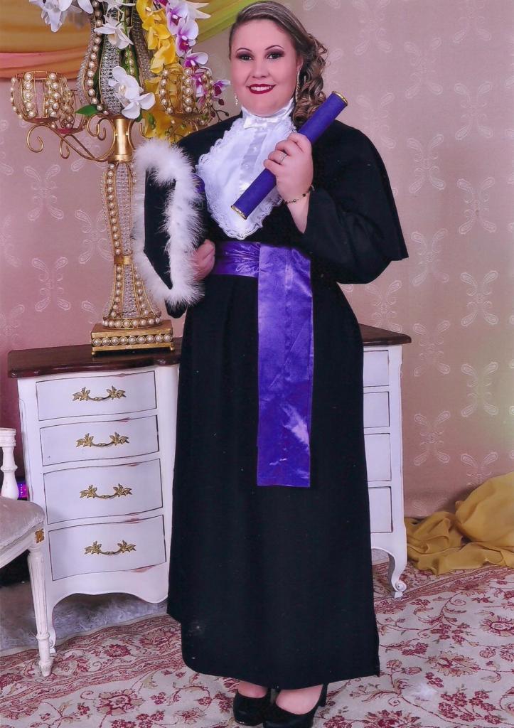 Foto vertical com mulher formanda vestida de toga e segurando canudo de formatura