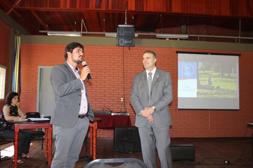 Foto horizontal, dois homens em pé. Um falando no microfone, o outro é o reitor Paulo Burmann