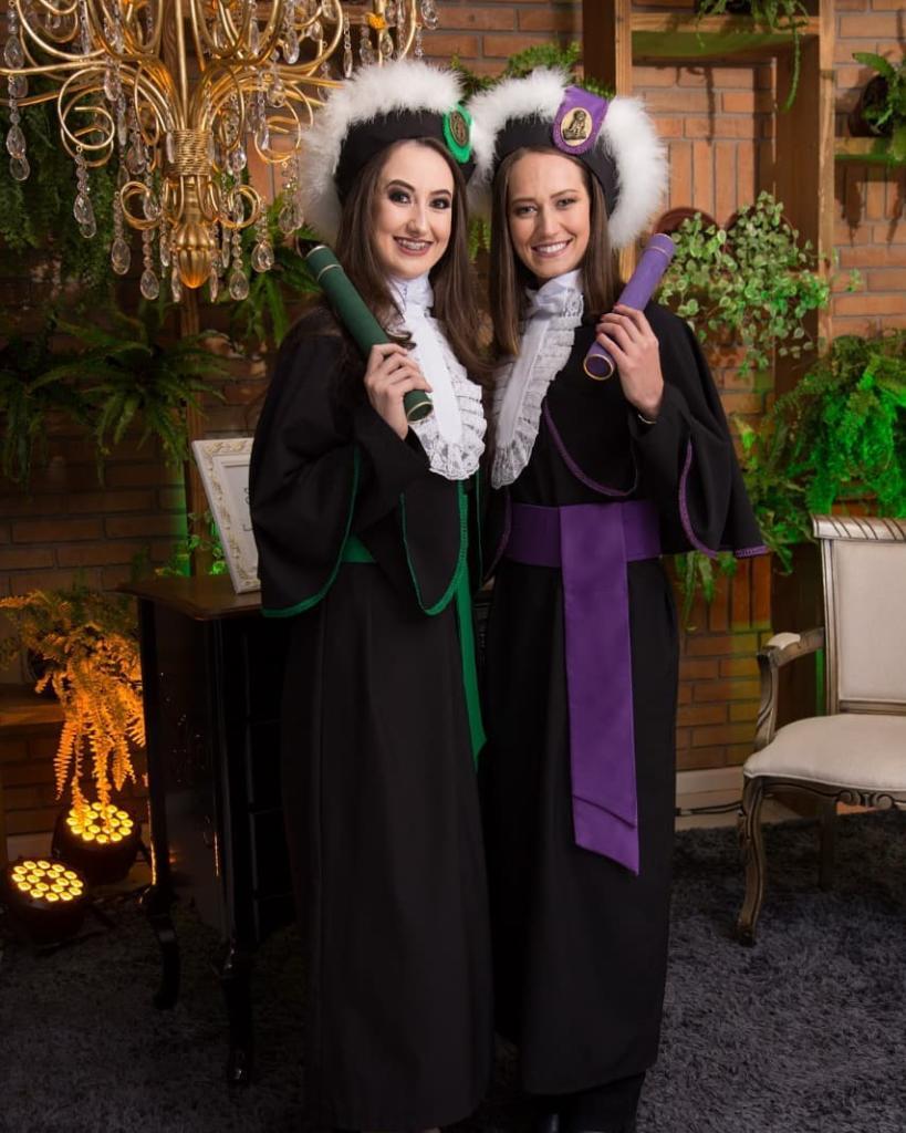 Foto vertical, duas formandas em pé, vestidas de toga, segurando canudos de formatura