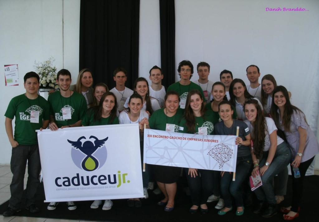 Foto horizontal, turma inteira de estudantes em pé segurando banner da empresa júnior Caduceu Jr