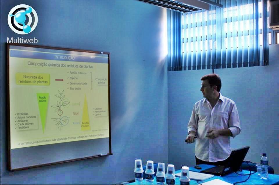 Foto quadrada de pessoa apresentando trabalho em frente à tela de projeção