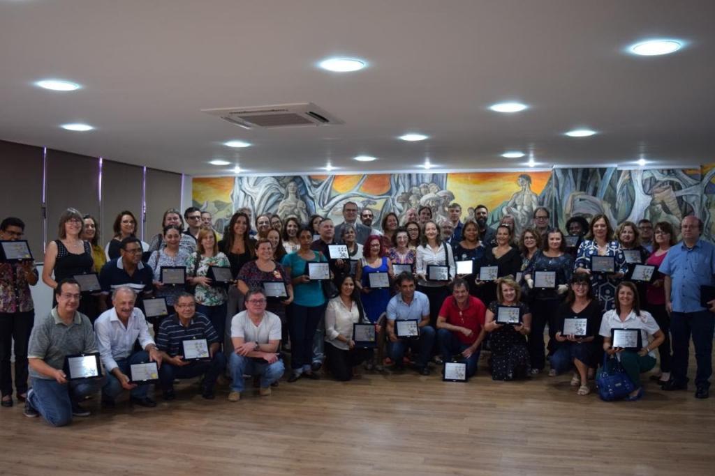 Foto aérea com diversas pessoas reunidas em frente a um mural segurando certificados de tempo de trabalho na UFSM