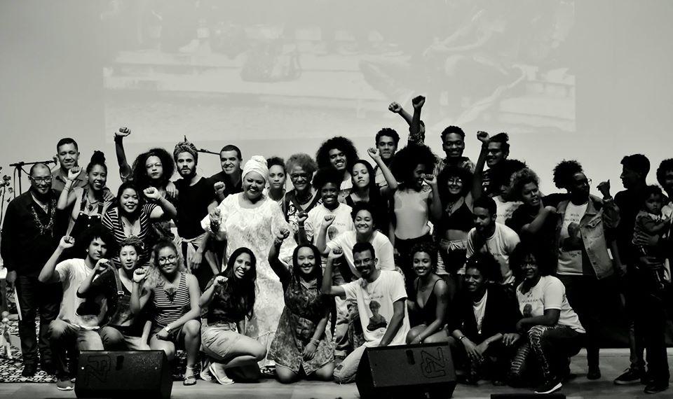 Foto horizontal em preto e branco com diversas pessoas no palco do Centro de Convenções durante evento Novembro Negro