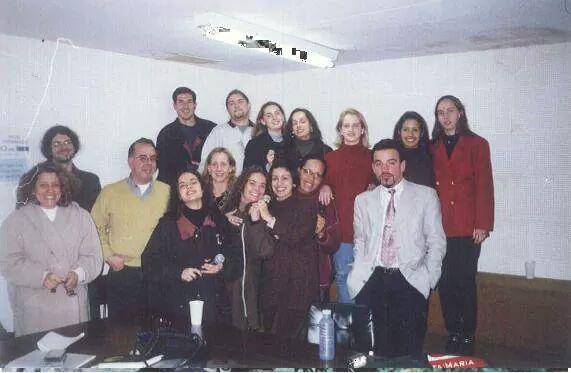 Foto horizontal com grupo de 14 pessoas, algumas sentadas outras em pé, numa sala branca