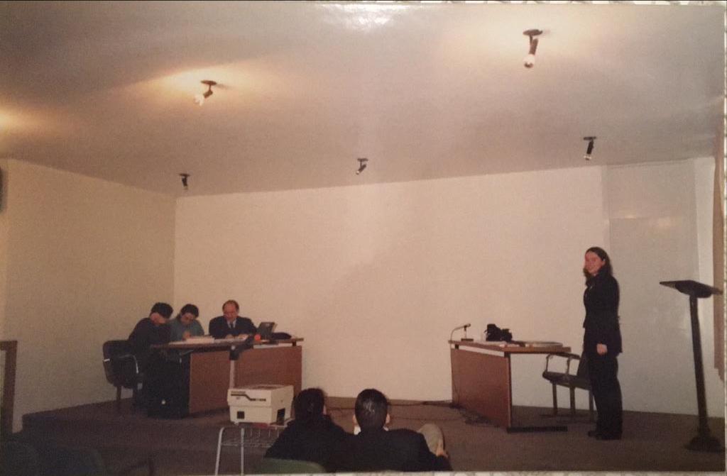 Foto horizontal, 3 pessoas sentadas em uma mesa e uma em pé apresentando trabalho