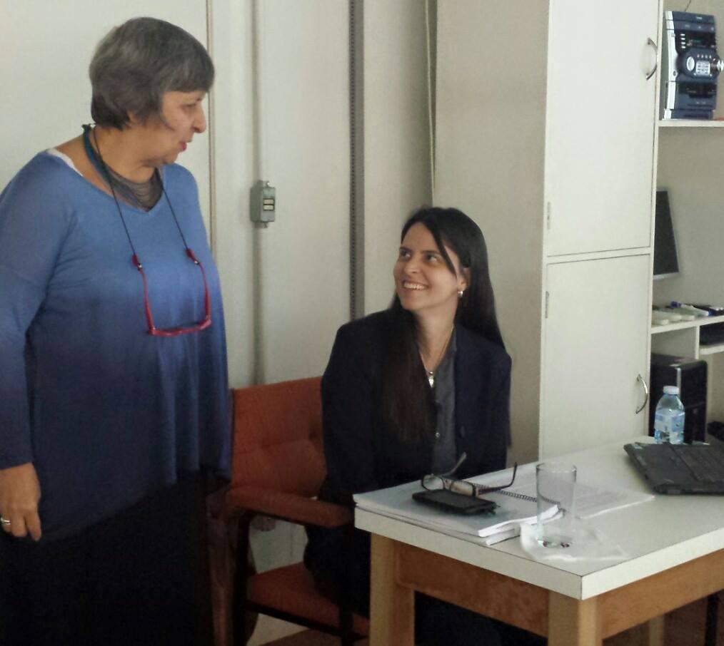 Foto horizontal, uma professora em pé olhando para uma estudante sentada em uma classe olhando de volta